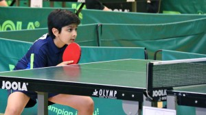 Aadil awaits in his returning position for the serve of his opponent on August 23, 2015. He competed in a Euro Mini which is the most prestigious TT championship in all of Europe for the Under 11 age group. This tournament took place in Schiltigheim, France and Aadil came in 6th place (photo courtesy Anand family).