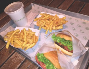 Shake Shack burgers are available with free lettuce and tomato toppings. Most burger toppings are free except for extra cheese, bacon, or Shack Sauce. Shake Shack's signature Crinkle Cut Fries are available with their blended cheddar cheese sauce as well as plain (photo by Grace Kelman).