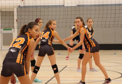 Eighth graders Sofia Salveson, Emma Whitman, and Hadley Bridges are getting ready for their teamate to serve the ball. On September 29 the girls played against the Egham Jaguars at ASL. The final score was 2-1 (Photo by Addie Griggs).